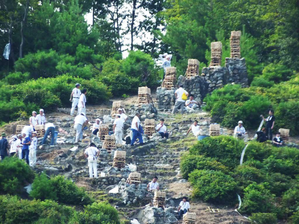 men preparing for the bonfires on Mt. Hidari Daimonji